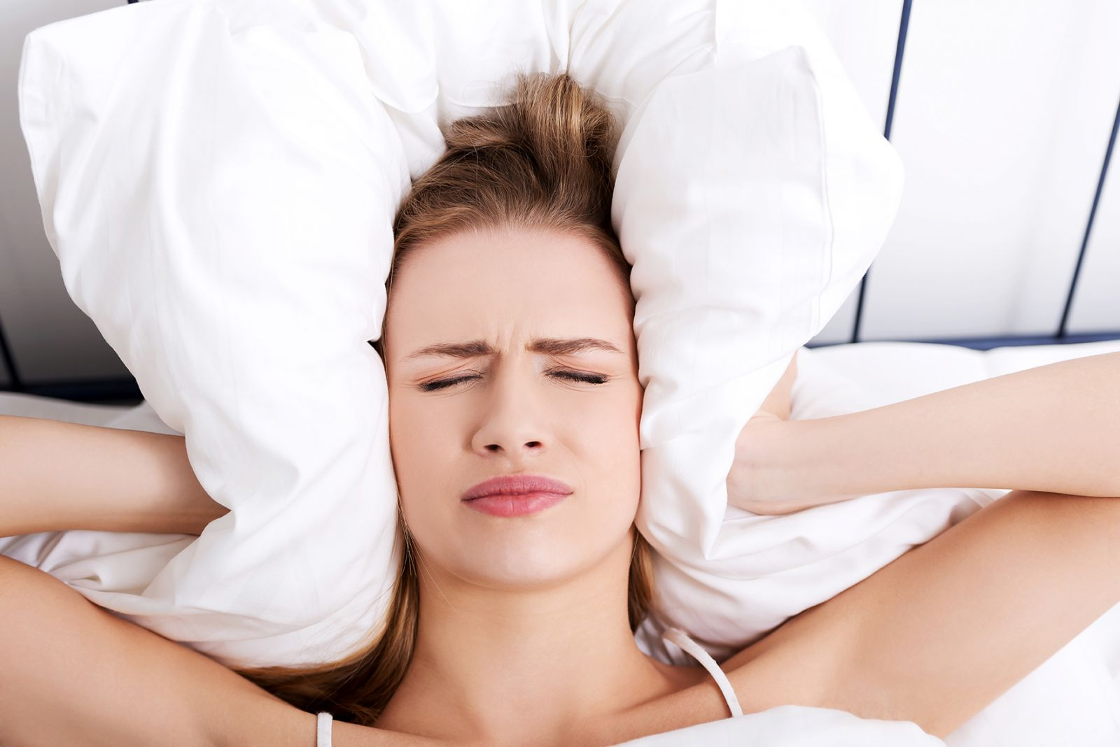 Woman holding Pillows over her ears to reduce sound